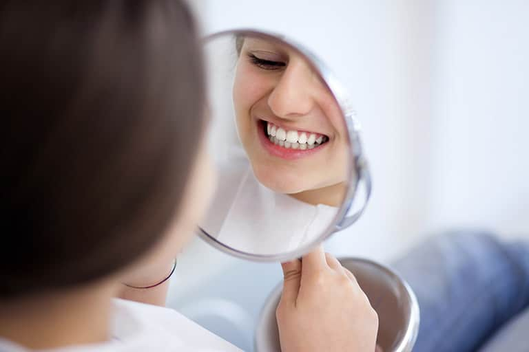 Woman Checking Teeth in Mirror